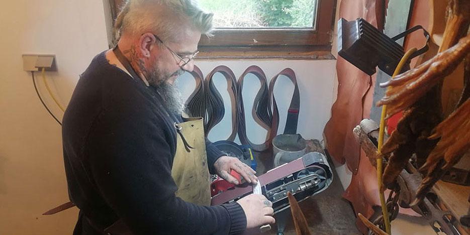 blecherner alex schleift messer auf schleifmaschine